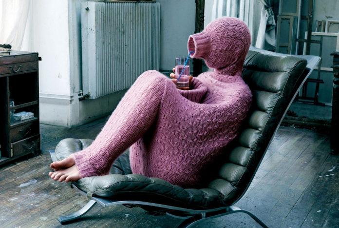 Osoba w różowym kombinezonie siedzi na fotelu bujanym