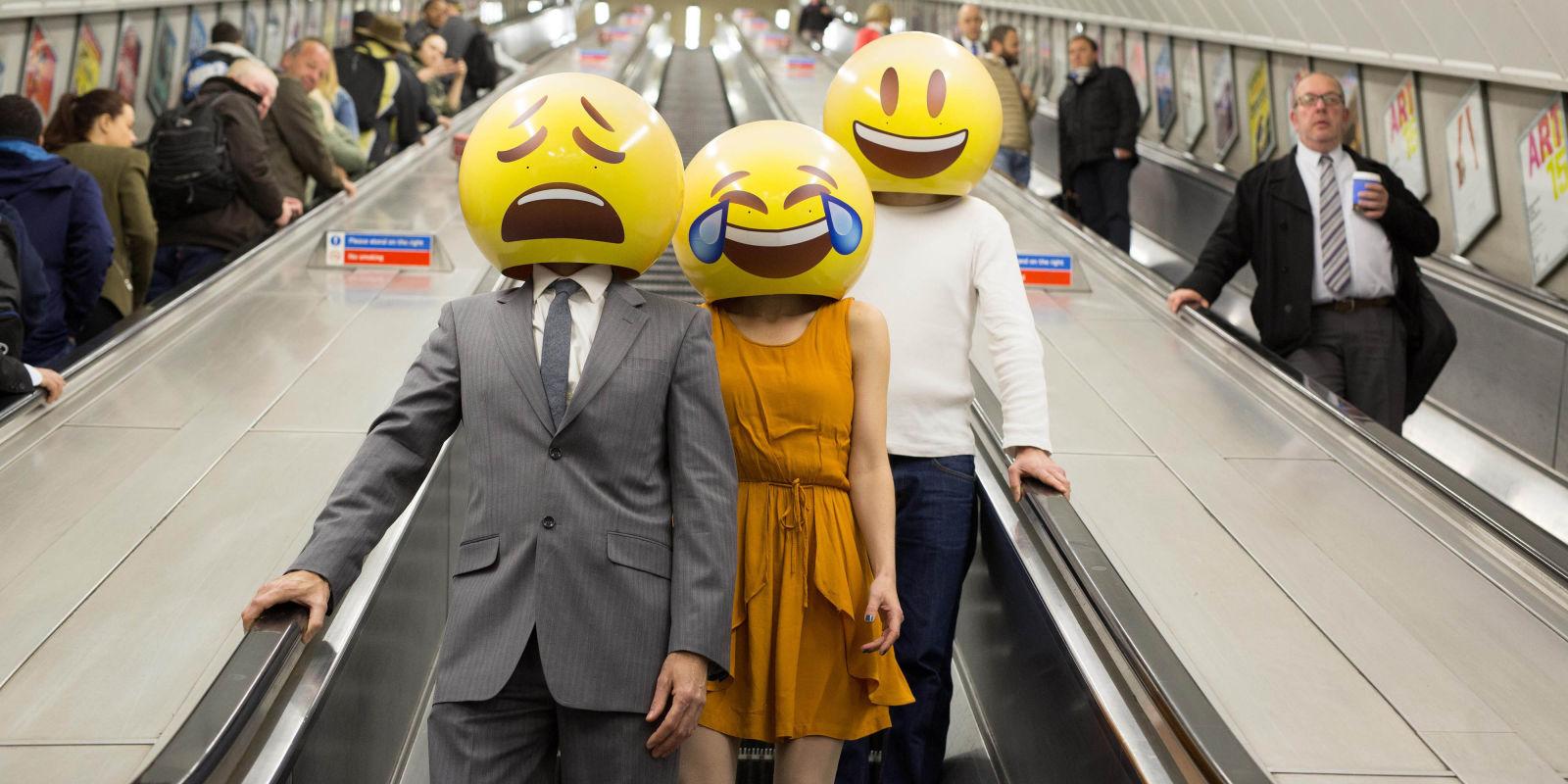 Trzy osoby na schodach ruchomych z emoji zamiast twarzy