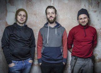Trzech chłopaków w bluzach na tle ściany
