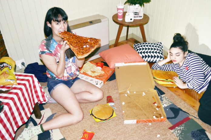 Dwie dziewczyny siedzą w pokoju na podłodze i jedzą pizzę