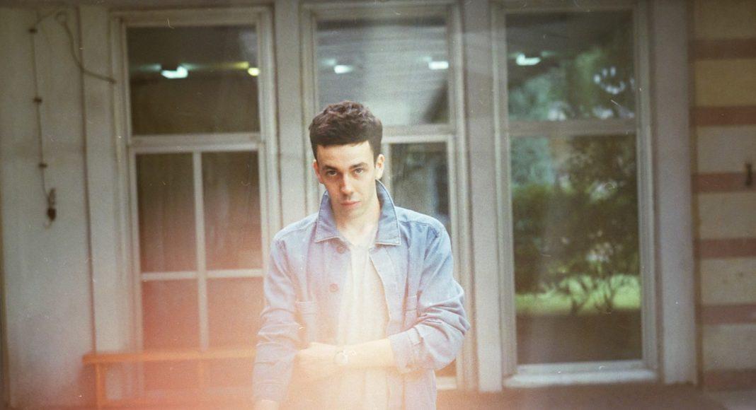 Mężczyzna w dżinsowej kurtce na tle białych okien