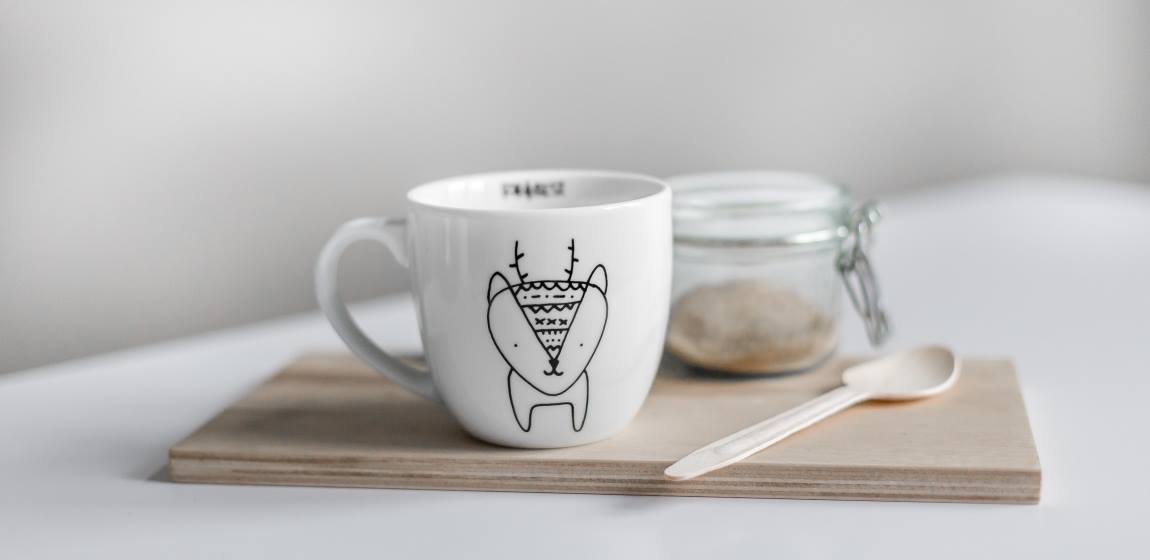 Biały kubek z printem kotka na drewnianej desce