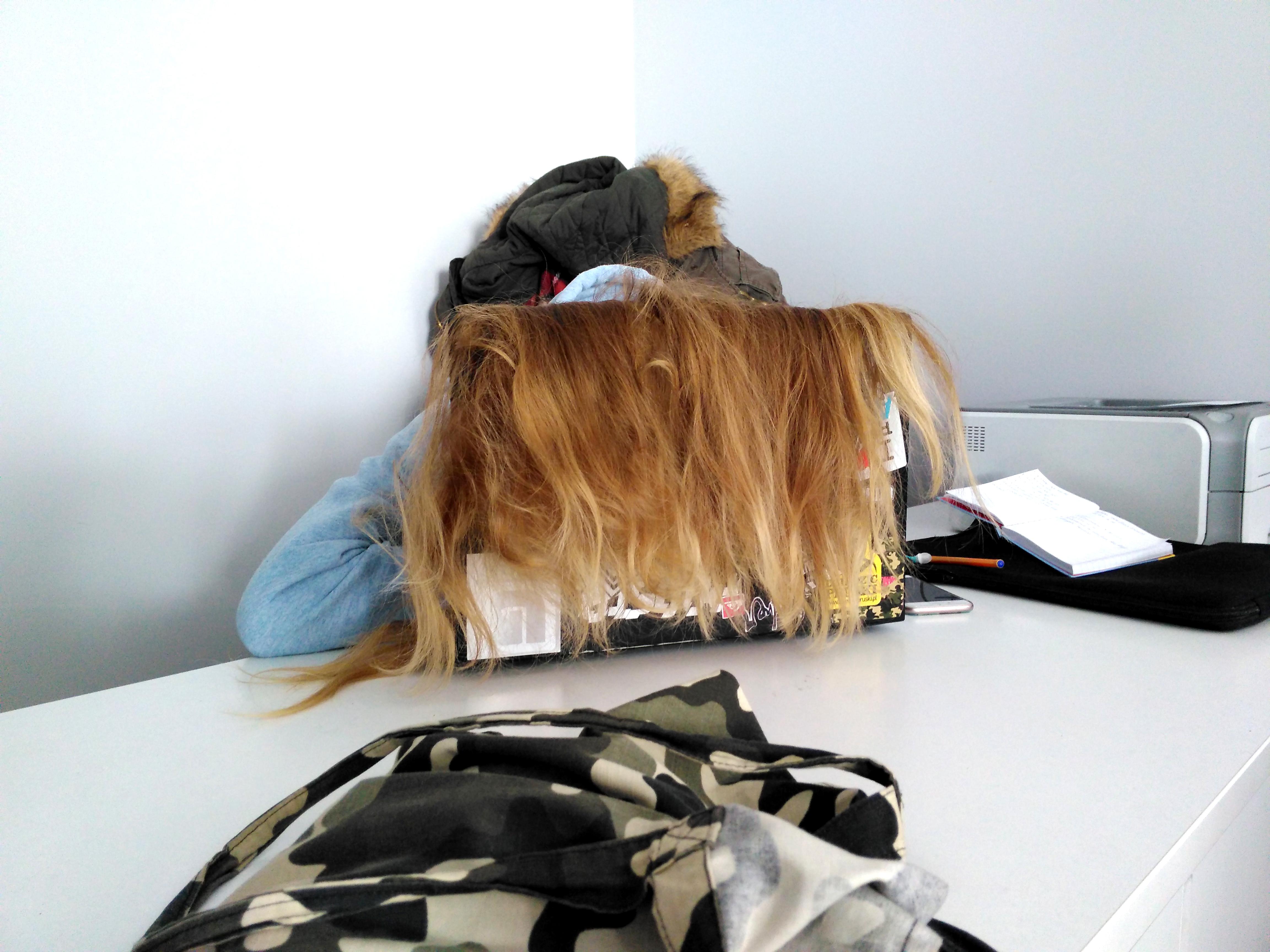 Blondynka siedzi przy biurku z włosami zarzuconymi na laptopa