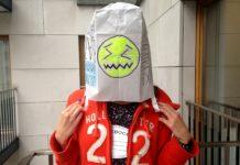 Dziewczyna w czerwonej bluzie z torbą na głowie