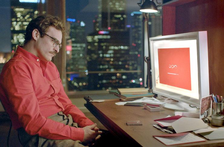 Mężczyzna w czerwonej koszuli i okularach siedzi przed komputerem