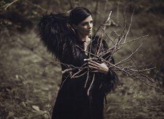Kobieta z ciemnymi włosami w ciemnym futrze trzyma gałęzie na tle łąki