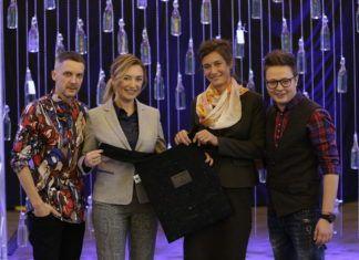 Trzy kobiety i mężczyzna trzymają czarną torbę