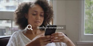 Kobieta z ciemnymi kręconymi włosami patrzy w smartfon