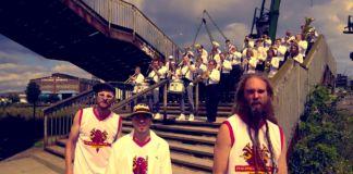 Grupa mężczyzn w jasnych koszulkach stoi na schodach