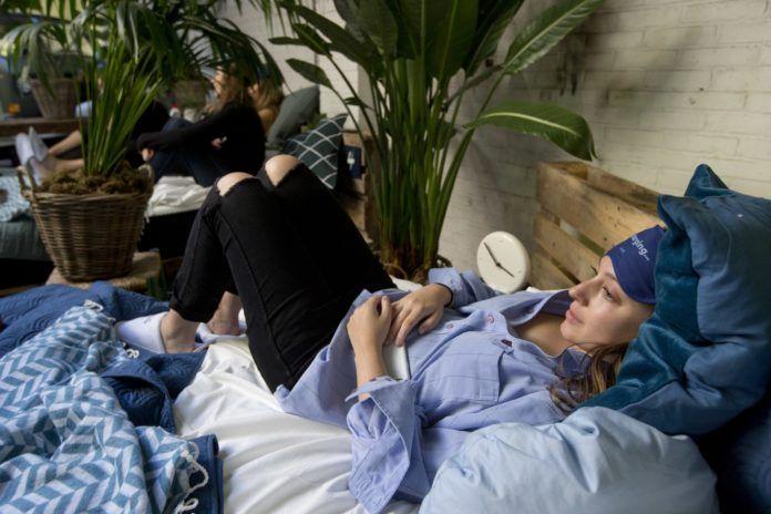 Kobieta w niebieskiej piżamie leży w łóżku