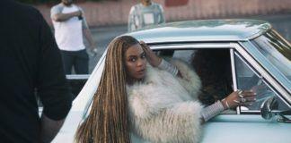 Kobieta z długimi włosami w jasnym futrze w samochodzie