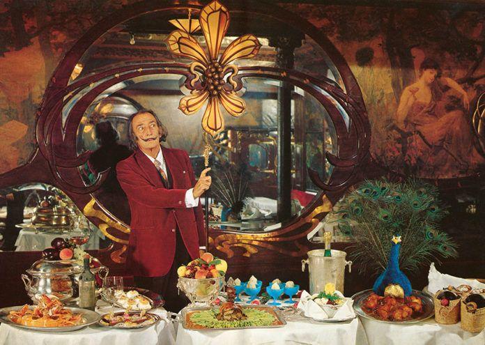Mężczyzna w czerwonej marynarce na tle stołu zastawionego jedzeniem