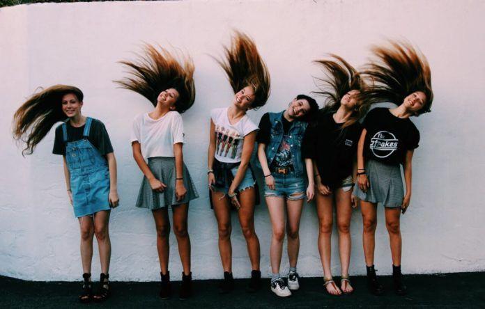 Dziewczyny z długimi włosami na tle ściany