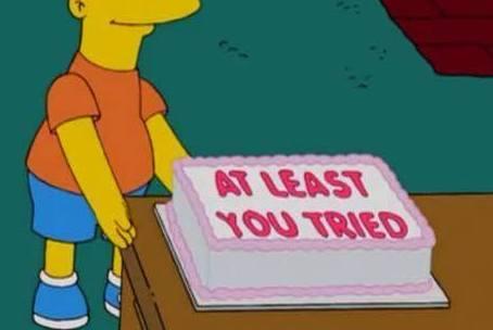 Żółta postać z kreskówki trzyma tort, napis: At least you tried