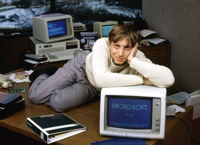 Mężczyzna w białym sweterku i szarych spodniach leży na komputerze