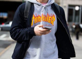 """Mężczyzna trzymający komórkę w ręku w szarej bluzie z napisem """"Thrasher"""""""