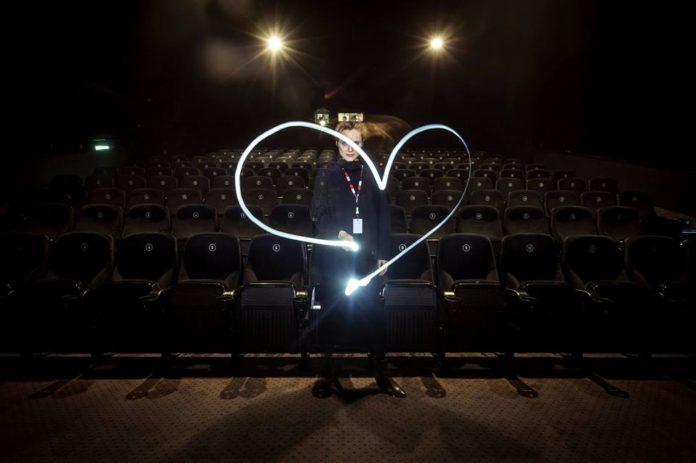 Kobieta ubrana na czarno rysuje w powietrzu serce światłem