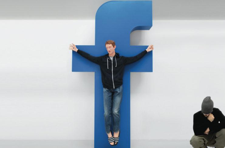 """Rzeźba przedstawiająca mężczyznę w bluzie wiszącego na niebieskiej literze """"F"""""""