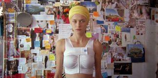 Kobieta w białym topie na tle ściany ze zdjęciami