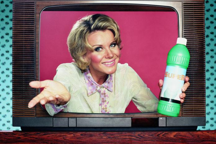 Kobieta z napojem w ręku wychodzi z telewizora