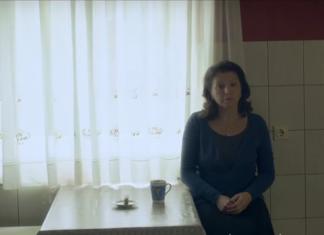 Kobieta w niebieskiej bluzce siedzi przy stole