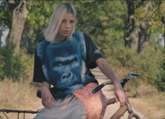 Blondynka w bluzce z gorylem na rowerze, w tle polna droga