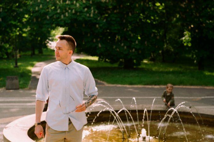 Mężczyzna w jasnej koszuli przy fontannie