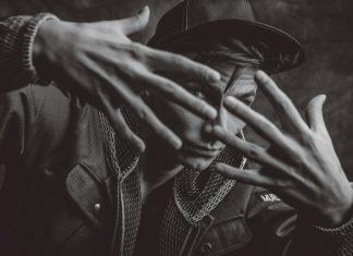 Mężczyzna w czapce zasłaniający się rękami