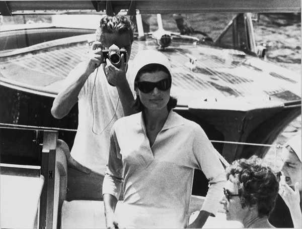 Kobieta w ciemnych okularach, za nią mężczyzna z aparatem