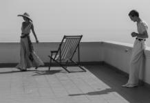 Mężczyzna i kobieta na balkonie, obok leżak