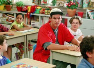 Chłopak w czerwonej koszulce siedzi w szkolnej ławce