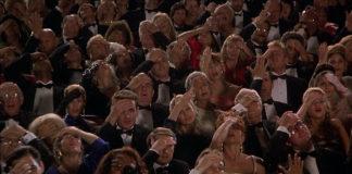 Siedzący na sali ludzie łapią się za głowę