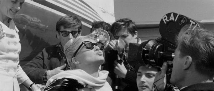 Blondynka w okularach wysyła całusa grupie paparrazi