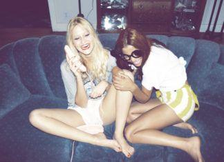 Dwie roześmiane dziewczyny siedzące na sofie i prowadzące rozmowę przez telefon