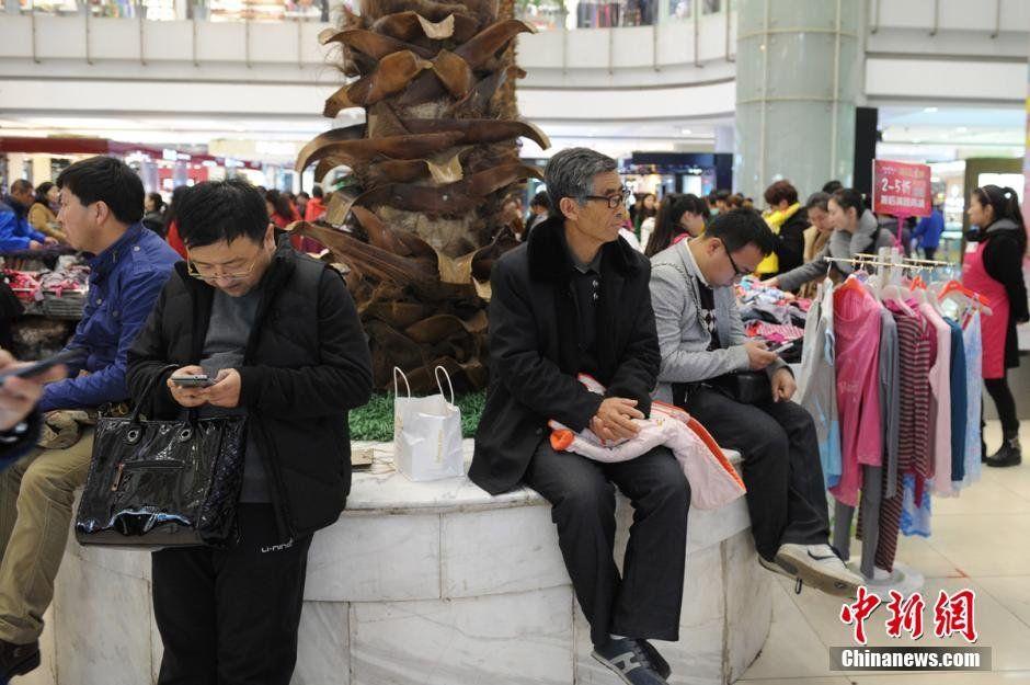 Znudzeni mężczyźni czekjący w centrum handlowym