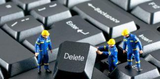 Grupa robotników usuwająca przycisk delete z klawiatury