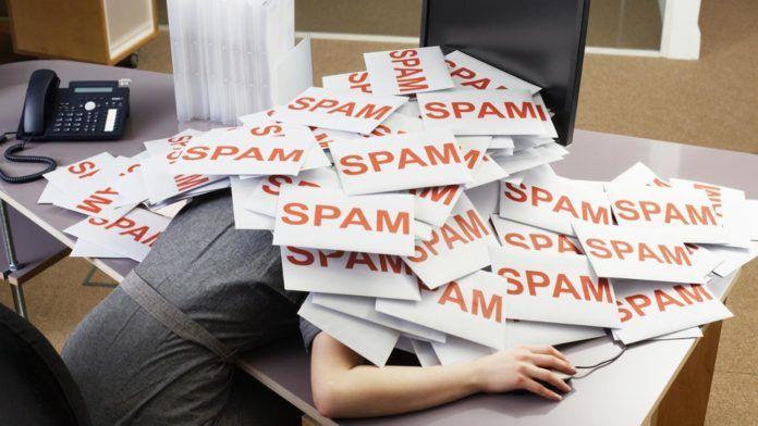 Kobieta leżąca głową na biurku, zasypana kartkami z napisem SPAM
