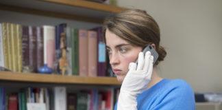Lekarka w niebieskim swetrze rozmawiająca przez telefon