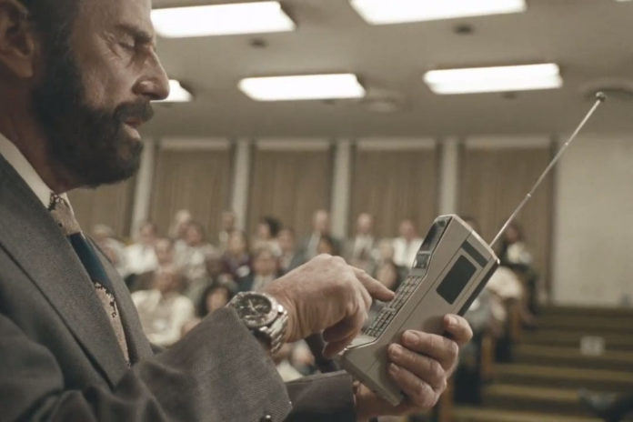 Mężczyzna trzymający stary telefon