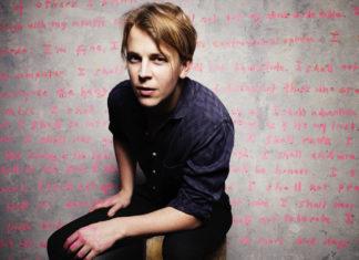 Blondyn w granatowej koszuli na tle ściany z różowymi napisami