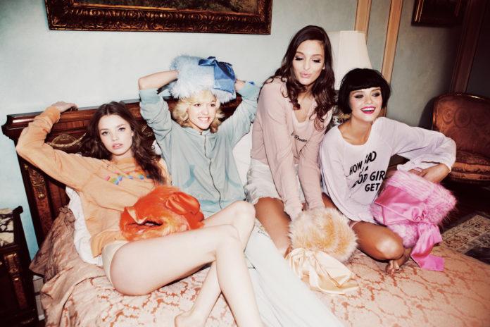Grupa zadowolonych przyjaciółek leżąca na łóżku