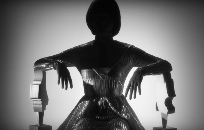 Metaliczno-czarna sylwetka siedzącej kobiety