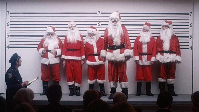 Sześciu mężczyzn przebranych za mikołajów stojących pod ścianą