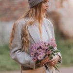 Dziewczyna ubrana w płaszcz i czapkę z kwiatami w ręku i przypiętą do paska torebką typu nerka, saszetka biodrowa
