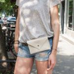 Kobieta ubrana w szarą koszulkę i jeansowe szorty, z przypiętą do paska przy spodniach torebką typu nerka, saszetka biodrowa