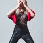 Dziewczyna w skórzanych spodniach, prześwitującej bluzce i narzucym czerwonym bolerko