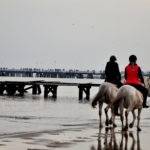 Para jadąca konno po plaży