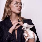 Dziewczyna z ciemnej marynarce, okularach typu awiator, trzymająca małego psa na ręku