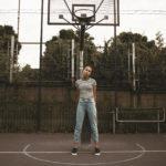 Dziewczyna ubrana w bluzkę w paski i jeansy, stojąca pod koszem do koszykówki