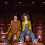 Para ubrana w stylu retro, siedząca na oparciach foteli kinowych